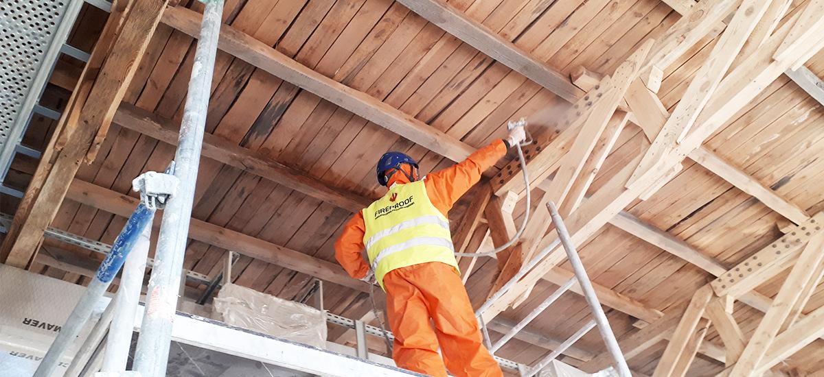 Zabezpieczenie konstrukcji drewnianych w budynku - pracownik w kombinezonie