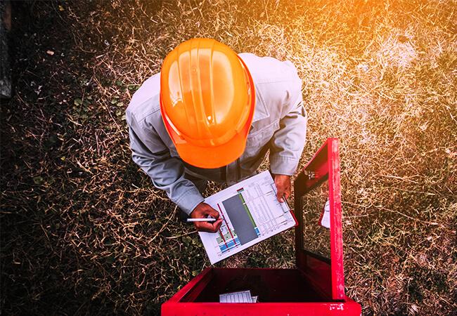 Pracownik w kasku dokonujący przeglądu systemu sygnalizacji pożaru